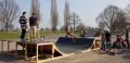 zwei Erwachsene testen mit ihren beiden Kindern die neue Miniramp auf der Skateranlage
