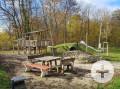 Waldspielplatz in der Waldsiedlung mit einer Essgruppe einem Holzhäuschen, einer Rutsche und einem Brunnen