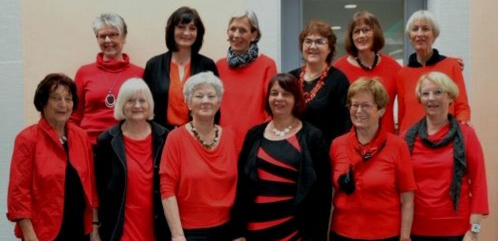 Das Team vom Bürgercafe bestehend aus 12 äteren Damen welche rot schwarz gekleidet sind und sehr freudig wirken
