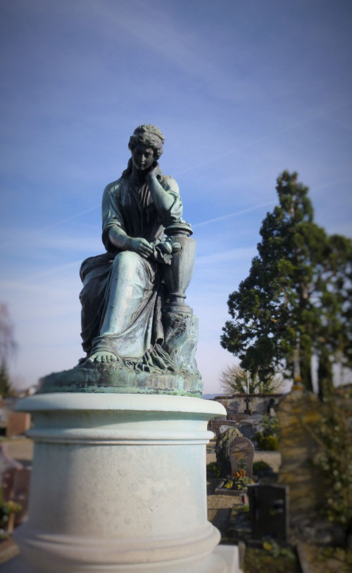 traurige Frauenfigur auf dem Friedhof